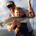 Young customer holding trout caught while fishing with Daytona Beach fishing guide, Capt. Mike Mann